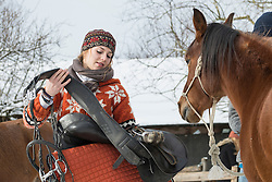 Young woman saddling her horse for riding in the barn, Bavaria, Germany