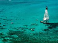 Alligator Lighthouse and snorkle boats over coral reefs, Florida Keys.