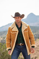 hot cowboy in a sheepskin jacket on a mountain range