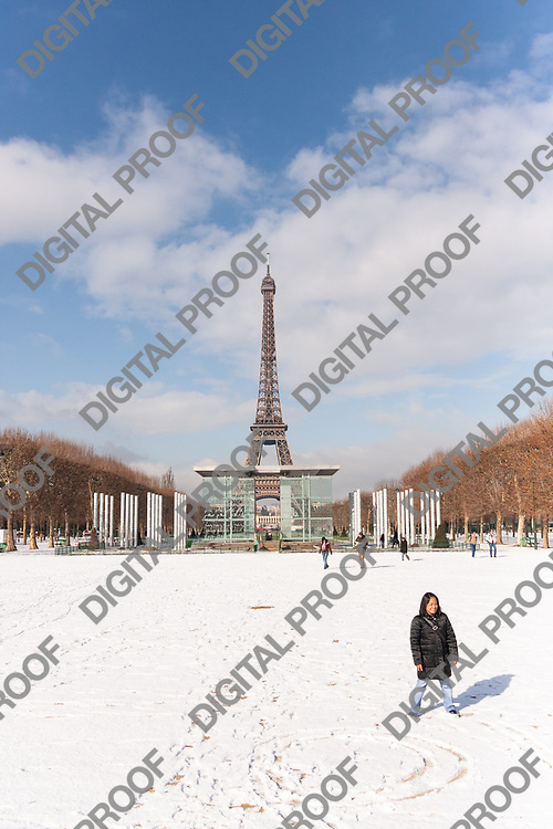 A tourist takes a photo with the eiffel tower in paris with snow during winter