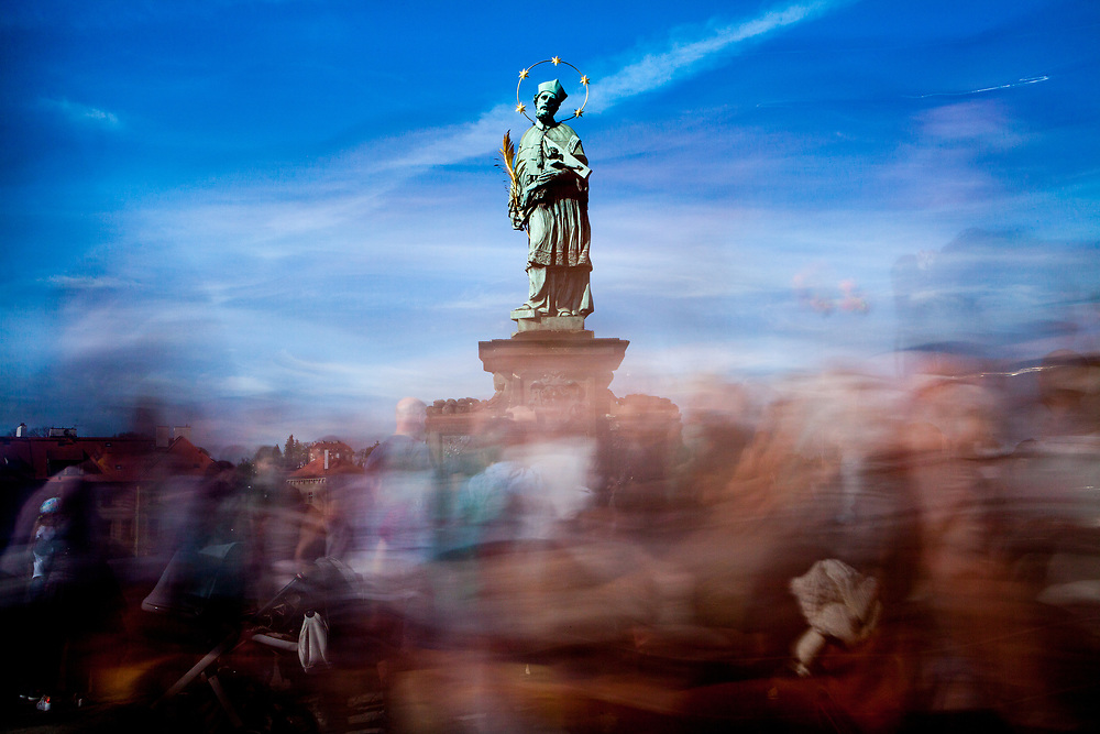 """Crowds are passing the statue of  """"John of Nepomuk"""" which is an outdoor sculpture, installed in 1683 on the north side of the Charles Bridge in Prague, Czech Republic."""