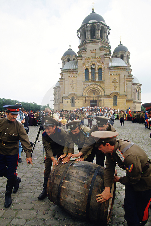 Russian Don Cossacks roll a barrel of homemade wine during a blessing at the Ascension Cathedral in Novocherkassk, Russia. The men are participating in the annual Cossack Festival gathering of units from around Russia.