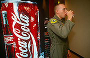 A United States Air Force pilot attending an escape and evasion course sips from a Coke can. With a Coca-Cola drinks vending machine behind him, loaded with Coke, the military airman is taking a break from a classroom briefing held at the United States Air Force's week-long survival course held at the Fairchild Air Force Base, Spokane, Washington. Its highly trained personnel conduct a survival, escape and evasion course which combat pilots and aircrew need to pass before re-joining their units for real-time warfare. Conducted, in hangars and the surrounding forests, it forms part of an extensive physical and psychological assessment of young aviators on active service.