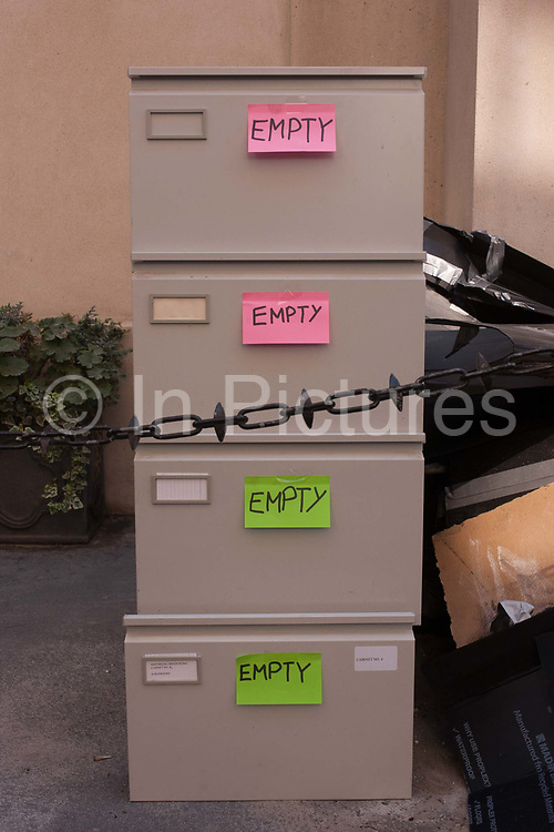Office furniture and fixtures including four drawers of a filing cabinet with post-it note stickers saying they contain nothing, await collection and recycling, on 24th August 2016, City of London, UK. Brought to this convenient location in the heart of the capitals financial district, founded by the Romans in the first Century, they will soon be removed by a contractor.