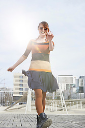 Young woman dancing in a playground, Munich, Bavaria, Germany