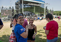 Chloe and Abbie show off their henna tattoos while waiting for Juniper to take the main stage as Soulfest 2017 gets underway on Thursday at Gunstock.  (Karen Bobotas/for the Laconia Daily Sun)