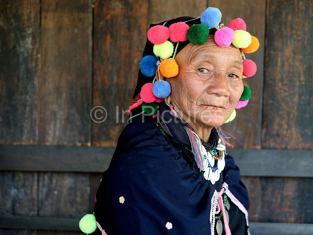 Portrait of a Yinbaw ethnic minority woman on 20th January 2016 in Kayah State, Myanmar. Myanmar is one of the most ethnically diverse countries in Southeast Asia with 135 different indigenous ethnic groups with over a dozen ethnic Karenni subgroups in the Kayah region. Yinbaw womens traditional costume is mainly black with brightly coloured pom-poms and similarly decorated head-dresses