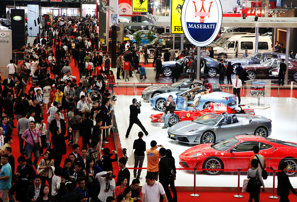 Visitors look at vehicles on display at the Auto Shanghai 2009 in Shanghai, China on 21 April 2009.  Automakers from across the world are increasingly focusing their efforts on China, the largest auto market in the world and the only major market with prospects of high growth rate.