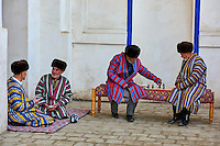 Ouzbekistan, Boukhara, hommes Ouzbek en chapane, aux habits traditionnels, jouant aux echecs // Uzbekistan, Bukhara, Unesco world heritage, Uzbek men playing chess in traditional clothes chapan