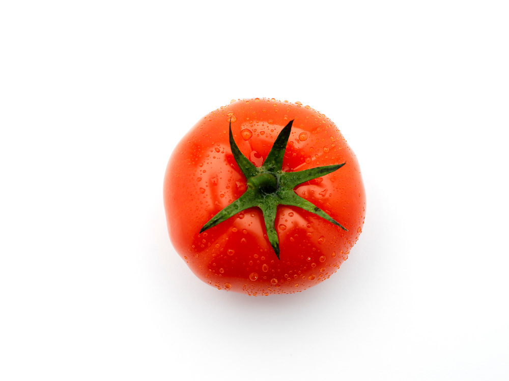 birds-eye view of a single red tomato on a white background