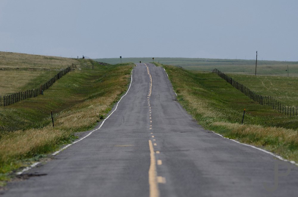 Typical rural road on the plains of eastern New Mexico.  Roads are very difficult to maintain because of the extreme weather changes and lack of people to pay taxes to maintain them.