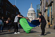 Two film location technicians struggle to fold away a background\reflector screen in front of St. Paul's cathedral, on 10th October 2018, in London, England.