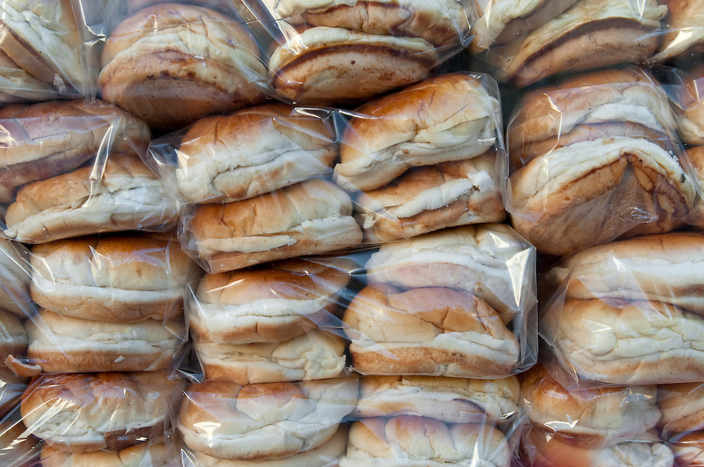 View of row of recently baked bread buns in bags ready to be sold.