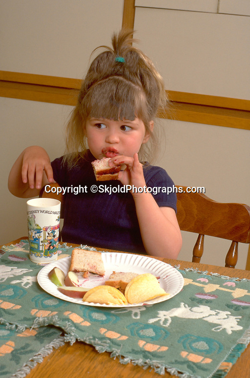 Girl eating lunch of peanut butter and jelly sandwiches age 3.  WesternSprings  Illinois USA