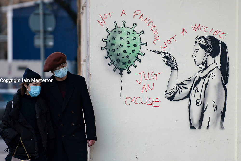 Street art of Covid-19 vaccination by street artist  The Rebel Bear in Edinburgh is vandalised by anti vaccination protester