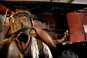 Billede 1: Brandmand med røgdykkermaske..Under en af testene af brandstationens eneste røgdykkerudstyr, springer elastikken der holder masken tæt til hovedet. En af brandmændene slår en hurtig knude, og håber det vil holde, hvis de får brug for udstyret i marken..