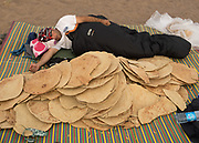 One of the driver sleeping next to all the traditional iranian flat bread that wil be eaten during the expedition.