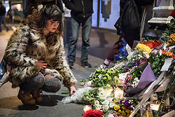 © Licensed to London News Pictures. 10/01/2017. London, UK. A woman lays flowers and lights a candle beneath a mural of David Bowie in Brixton, south London, to commemorate the first anniversary of the star's death. Photo credit: Rob Pinney/LNP