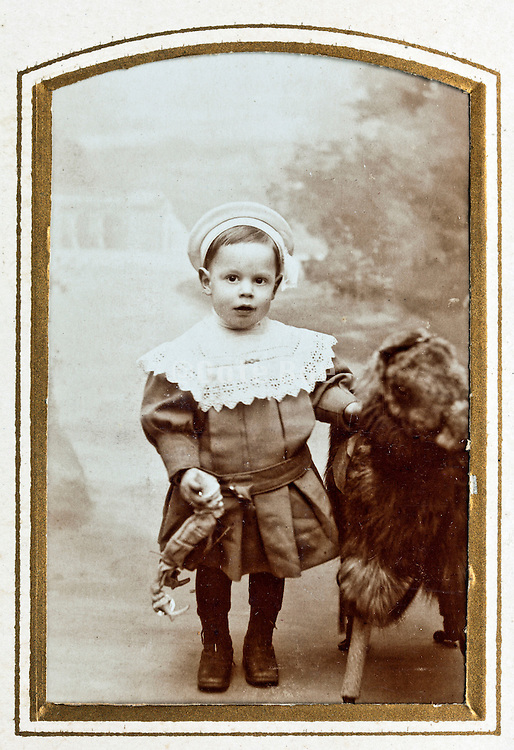 little child in 1900s studio setting with a toy pet