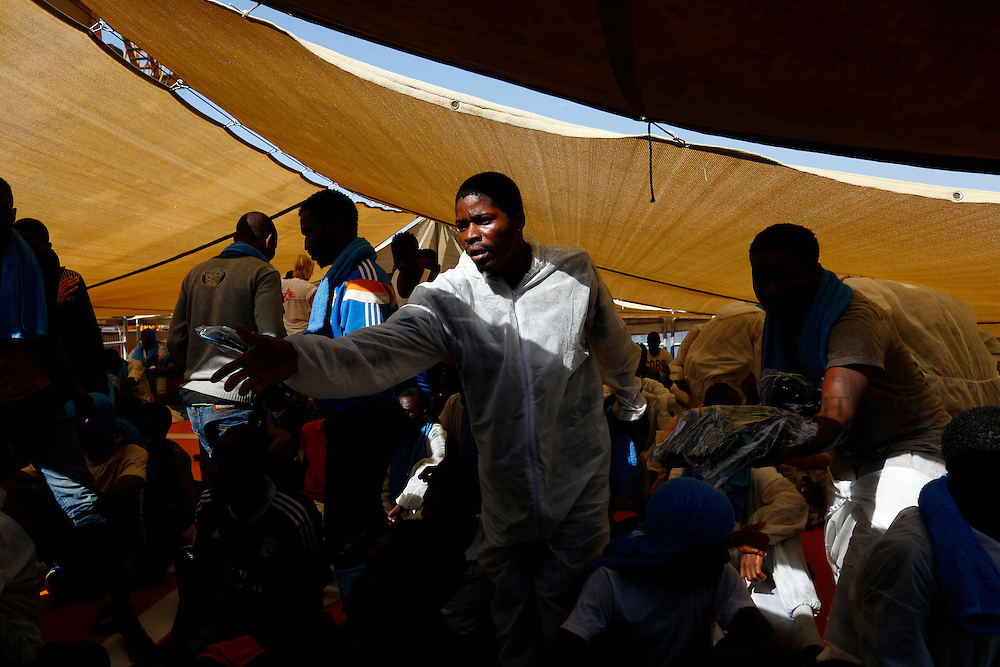 A Sub-Saharan migrant reaches out for sandals being distributed by Medecins san Frontiere (MSF) on the Migrant Offshore Aid Station (MOAS) ship MV Phoenix in Vibo Valentia, Italy, July 31, 2015.  195 migrants who were rescued off Libya on Wednesday arrived in Italy on Friday afternoon. The Phoenix, manned by personnel from international non-governmental organisations MSF and MOAS, is the first privately funded vessel to operate in the Mediterranean.<br /> REUTERS/Darrin Zammit Lupi <br /> MALTA OUT. NO COMMERCIAL OR EDITORIAL SALES IN MALTA