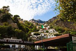 Positano, Italy, September 16 2017. An Italian flag flies in the breeze beneath the mountainside buildings of Positano, Italy. © Paul Davey