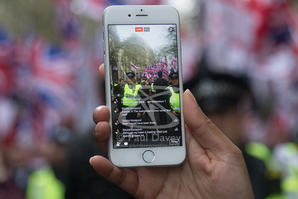 London, April 1st 2017. A Muslim woman live streams as protesters from nationalist and anti-Islamic group Britain First demonstrate in London following the Westminster terror attack of March 22nd.