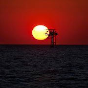 Solar power or oil? Oil platform near Galveston, Texas, at sunset in the Gulf of Mexico. here are nearly 5,000 functioning oil platforms in the Gulf of Mexico, and 27,000 abandoned wells.
