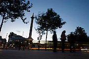 As traffic blurs past, silhouetted pedestrians stand beneath trees and Nelson's Column in Trafalgar Square .