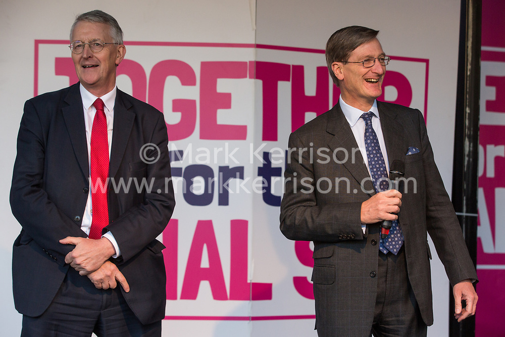London, UK. 19 October, 2019. Dominic Grieve (r), Independent MP for Beaconsfield, seen here with Hilary Benn (l), Labour MP for Leeds Central, addresses hundreds of thousands of pro-EU citizens at a Together for the Final Say People's Vote rally in Parliament Square as MPs meet in a 'super Saturday' Commons session, the first such sitting since the Falklands conflict, to vote, subject to the Sir Oliver Letwin amendment, on the Brexit deal negotiated by Prime Minister Boris Johnson with the European Union.