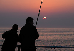 © Licensed to London News Pictures.02/07/15<br /> Saltburn by the Sea, UK. <br /> <br /> Fisherman stand on the end of the pier at Saltburn beach at sunrise.<br /> <br /> Photo credit : Ian Forsyth/LNP
