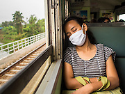 20 MARCH 2015 - CHACHOENGSAO, CHACHOENGSAO, THAILAND:   A passenger sleeps on a third class train leaving Bangkok for Kabin Buri. People in rural Thailand frequently wear masks because Thai farmers burn out their fields in March and April and there is smoke and particulates in the air. The State Railways of Thailand (SRT), established in 1890, operates 4,043 kilometers of meter gauge track that reaches most parts of Thailand. Much of the track and many of the trains are poorly maintained and trains frequently run late. Accidents and mishaps are also commonplace. Successive governments, including the current military government, have promised to upgrade rail services. The military government has signed contracts with China to upgrade rail lines and bring high speed rail to Thailand. Japan has also expressed an interest in working on the Thai train system. Third class train travel is very inexpensive. Many lines are free for Thai citizens and even lines that aren't free are only a few Baht. Many third class tickets are under the equivalent of a dollar. Third class cars are not air-conditioned.    PHOTO BY JACK KURTZ