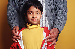 Portrait of young boy with adult's hands placed on his shoulders,