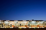 """An wide exterior view of Heathrow Airport's Terminal 5 building in West London. Created by the Richard Rogers Partnership (now Rogers Stirk Harbour and Partners). As the last light of the day fades, the brightness of terminal lights shine through massive panes of window glass. At a cost of £4.3 billion, the 400m long T5 is the largest free-standing building in the UK with the capacity to serve around 30 million passengers a year. The Terminal 5 public inquiry was the longest in UK history, lasting four years from 1995 to 1999. From writer Alain de Botton's book project """"A Week at the Airport: A Heathrow Diary"""" (2009). ..."""