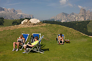 Sunbathing hikers in deckchairs in the Pralongià above San Cassiano-St. Kassian in the Dolomites, south Tyrol, northern Italy. In winter, the Pralongià meadows are the heart of Alta Badia's skiing area. Hiking trails lead across the high alpine pastureland between Corvara and San Cassiano (St. Kassian) with hilly upland meadows with vast mountain pastures and many old hay huts, a pretty group of trees at the edges of the meadows, and the beautiful shapes of the surrounding mountains, which include the Gruppo di Sella (Sellastock) Massif, Sassongher, Monte Cavallo (Heiligkreuzkofel), Cunturines and Lagazuoi.