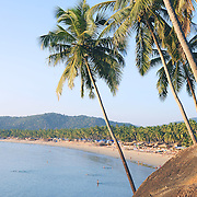 Palm trees with beautiful seascape on background with mountains, bay, sand beach and shacks (Palolem Beach)