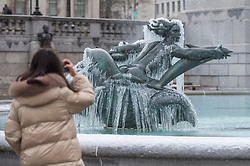 © Licensed to London News Pictures. 09/02/2021. LONDON, UK. A woman views one of the ice covered frozen fountains in Trafalgar Square during light snow flurries as the cold weather brought on by Storm Darcy continues.  Photo credit: Stephen Chung/LNP