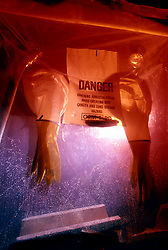 Stock photo of a sealed off partition with arm holes and gloves for handling asbestos