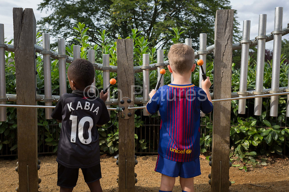 Young boys experiment with strike sound pipes to make musical notes in the Horniman Museums Sound Garden, on 24th August 2017, Forest Hill, London, England.