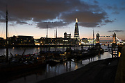 View looking across the River Thames over Hermitage Moorings to the skyline of Tower Bridge and The Shard in London, UK. One of the World's most famous cityscapes from Wapping towards this most iconic of skylines.