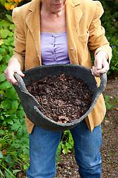 Carol Klein with tub of leaf mould
