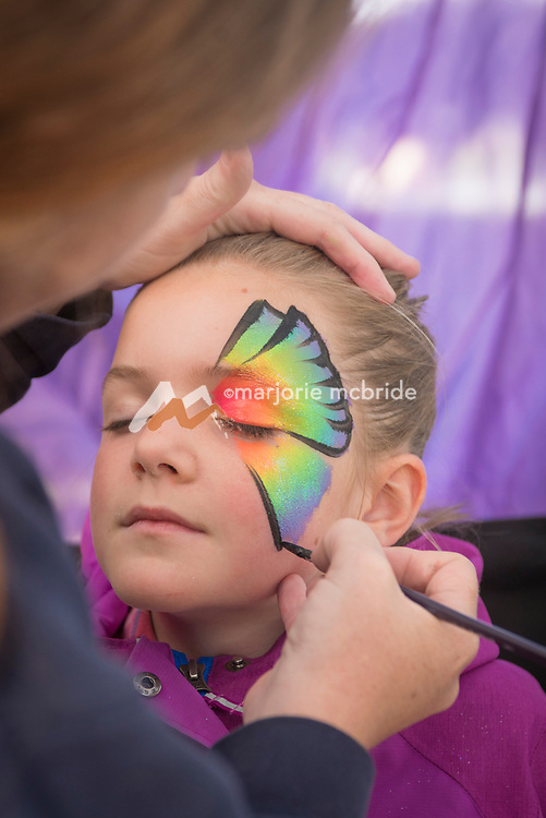 Action shot of a little girl having a butterfly painted on her face at the Thousand Springs Art Festival at Ritter Island near Hagerman, Idaho. MR