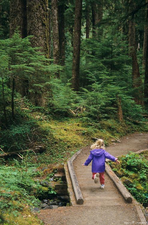 North America, USA, Washington, Olympic National Park. Sol duc falls.  Girl (age 4) crosses boardwalk on trail   MR