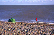 Person fishing from the beach on the North Sea coast, Shingle Street, Suffolk, England, UK