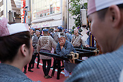 A mn rests as mikoshi are carried around the streets of Asakusa, on the evening of the first day of the Sanja matsuri. Asakusa, Tokyo, Japan. Friday May 13th 2016 The Sanja matsuri is one of the biggest festivals in Japan. Taking place over the 3 days of the second weekend of May (May 13th to 15th) it features many mikoshi, or portable shrines, that are carried around by local groups to bring blessings and prosperity to their neighbourhoods
