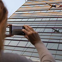 Viewer takes pictures with her mobile phone as members of the Bandaloop company from USA perform on the glass wall of an office building during the the CAFe Contemporary Art Festival in downtown Budapest, Hungary on Oct. 20, 2017. ATTILA VOLGYI