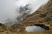 Hikers and porters hiking the Inca Trail pass a small alpine lake on their journey to Machu Picchu, Peru on September 20, 2005.