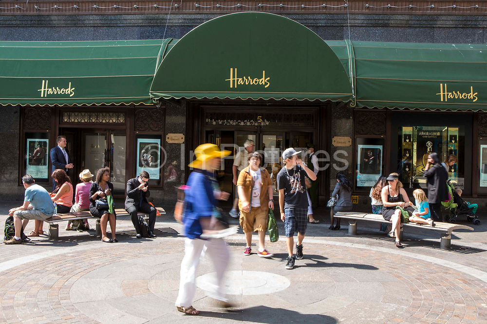 Tourists shoppers exit the world famous retail store Harrods via door 5 in Knightsbridge, London, United Kingdom.  Some other customers sit on the benches outside the shop enjoying the sunshine.