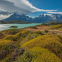 """A wind-swept lenticular cloud soars over the Grand Tower of Paine, the Horns of Paine, Pehoe Lake and bushes called """"mother-in-law's cushion"""" in Torres del Paine National Park, Chile."""