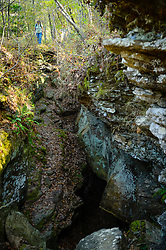 A hiker explores one of the many crevices and caves along the Devil's Den Self-Guided trail in Devil's Den State Park.<br /> <br /> Devil's Den State Park is an Arkansas state park located in the Lee Creek Valley of the Boston Mountains in the Ozarks. Devil's Den State Park contains one of the largest sandstone crevice areas in the U.S. The park contains many geologic features such like crevices, caves, rock shelters, and bluffs. The park is also known for its well-preserved Civilian Conservation Corps (CCC) structures built in the 1930s. These structures, still in use today include cabins, trails, a dam, and shelter.<br /> <br /> Devil's Den State Park has approximately 64 miles of trails that are popular with hikers, mountain bikers and horseback riders. One popular trail is the Devil's Den Self-Guided Trail (1.5 miles long) that passes by Devil's Den Cave (550 feet), Devil's Den Ice Box, numerous rock crevices, and Twin Falls. Another popular trail is the Yellow Rock Trail (3.1 miles) that leads to expansive views of the Lee Creek Valley.