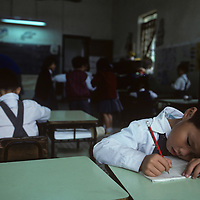 China, Hong Kong, Schoolboy works in school at Sheung Shui in New Territories